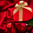 图库照片: Valentine Red Hear Gift on Red Silk Background