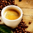 Coffee Espresso. Cup Of Coffee with Beans and Green Leaf — Stock Photo #40235097