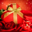 Stock Photo: Valentine Red Hear Gift and Red Rose Flower over Red Silk