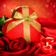 Valentine Red Hear Gift and Red Rose Flower over Red Silk — Stock Photo #40235401