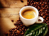 Coffee Espresso. Cup Of Coffee with Beans and Green Leaf — Stock Photo