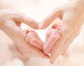 Tiny Newborn Baby's feet on female Heart Shaped hands closeup — Stock Photo