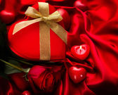 Valentine Red Hear Gift and Red Rose Flower over Red Silk — Stock Photo