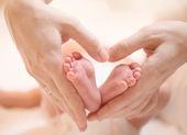 Tiny Newborn Baby's feet on female Heart Shaped hands closeup — Stock Photo
