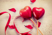 Elegant red satin ribbon and couple of red hearts — Stock Photo