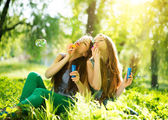 Teenage girls blowing soap bubbles — Stok fotoğraf