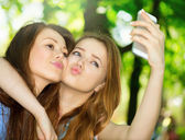 Teen friends taking photos with a smartphone. — Stock Photo
