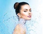 Girl under splash of water — Stockfoto