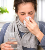 Sneezing woman into tissue. — Stock Photo
