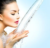 Smiling girl under splash of water — Foto Stock