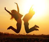 Silhouette of a  girls jumping over sunset — Foto Stock
