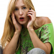 The young beauty is surprised with news in a phone conversation — Stock Photo