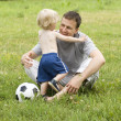 Stock Photo: Father playing football with his son