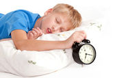 Sleeping kid with alarm clock in front — Stock Photo