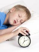 Niño dormido con reloj despertador en frente — Foto de Stock