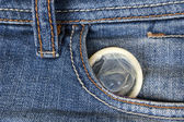 Condom peeking out from jeans pocket — Stock Photo