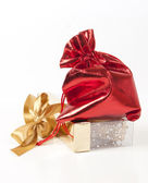 Red bag with gifts and a gold bow — Stock Photo