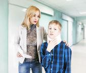 Mamma med son på sjukhuset. skada av en hals. — Stockfoto