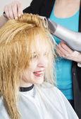 Hairdresser dries hair — Stock Photo