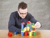 Muž staví dům hraček bloků — Stock fotografie
