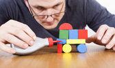 Man creating the car of toy blocks — Stock Photo