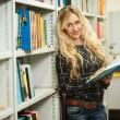 Young beautiful blonde girl in a library — Stock Photo