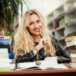 Young beautiful blonde girl in a library — Stock Photo #35303807