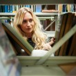 Young beautiful blonde girl in a library — Stock Photo #35303825