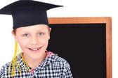 Graduate boy in cap with blackboard in background — Stock Photo
