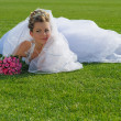 Young beautiful bride lying on green grass — Stock Photo #18712627