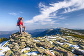 Hiker girl with backpack  in a mountains — Stock Photo