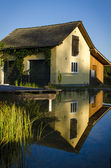Old house inverse in lagoon — Stock Photo
