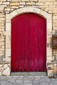 Old red door against stone wall — Stock Photo