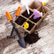 Garden tools (shovel, rake, peat pots ) on old wooden background — Stock Photo