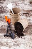 Garden tools (shovel, rake, peat pots ) on old wooden background — Stock Photo