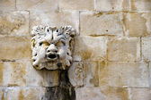 Stone mask figure on ancient fountain, architectural detail of o — Stock Photo