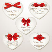 Set of elegant heart shaped cards with red bows — Stockvector