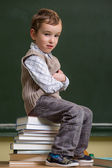 Schoolboy sitting on a pile of books in the classroom — Foto de Stock