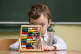 Boy in school working with abacus — Stock Photo