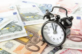 Clock and euro banknotes — Stock Photo