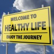图库照片: Road sign with words Welcome to healthy life on blue sky background