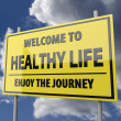 Photo: Road sign with words Welcome to healthy life on blue sky background