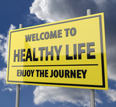 Road sign with words Welcome to healthy life on blue sky background — Stok fotoğraf