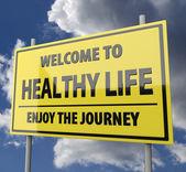 道路标志与字欢迎光临健康生活在蓝色天空背景上 — 图库照片