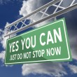 图库照片: Yes you cjust do not stop now words on road sign green