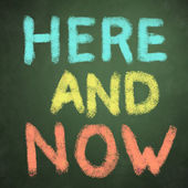 Here and now words on green chalkboard background — Stockfoto