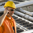 Worker with helmet and sunglasses talking on mobile phone in front of cooling plant — Lizenzfreies Foto