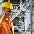 Worker with helmet and sunglasses talking on mobile phone in front of industrial plant — Стоковая фотография