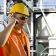 Foto Stock: Worker with helmet and sunglasses talking on mobile phone in front of oil plant