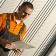 Worker with paper folder in front of industrial hall — Stock Photo